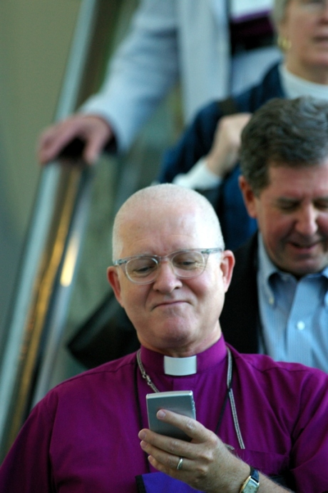 he Rt. Rev. George Wayne Smith, Bishop of Missouri, checks a message during General Convention while on an escalator in the Anaheim Convention Center